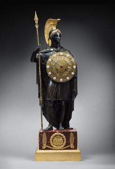 A LATE EMPIRE MANTEL CLOCK REPRESENTING PALLAS ATHENA ATTRIBUTED TO GÉRARD-JEAN GALLE, PARIS, DATE CIRCA 1820 Gérard-Jean Galle (attributed to) Gilt and patinated bronze and red marble Height of figure: 70 cm; overall height 87 cm