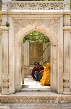 A couple talks behind a marble arch in Nizamuddin.