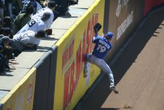 Toronto Blue Jays right fielder Jose Bautista leaps against the padded wall to catch New York Yankees batter Brett Gardner's fly ball in the first inning of their opening day game at Yankee Stadium in New York on Monday.  - CHANG W. LEE, THE NEW YORK TIMES