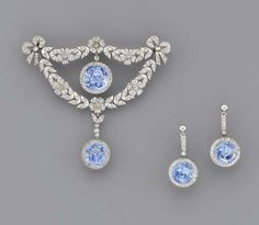 A BELLE EPOQUE SAPPHIRE AND DIAMOND BROOCH AND A PAIR OF EAR PENDANTS   The central circular-cut sapphire and diamond cluster drop within the rose-cut diamond floral wreath with diamond bow terminals, suspending a sapphire and diamond drop, earrings en suite, adapted, mounted in platinum, circa 1905, brooch 6.7 cm. high, in original cream leather fitted case