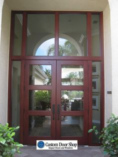 Make a statement with this extra large front entrance! Contemporary mahogany double wood doors with glass inserts, large pulls, sidelights and transom. Light and airy.
