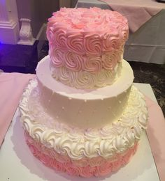 This gorgeous 3-tier wedding cake is adorned with hand piped pink buttercream ombré roses on the first and third tiers, and the center tier is quilted with pearls. This is a beautiful modern take on a classic style wedding cake. Products by Palermo's Custom Cakes & Bakery