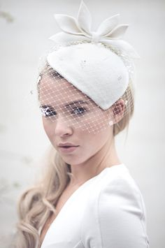 Siobhán is a birdcage veil cocktail hat in peachbloom felt. A vintage style wedding hat which has been hand shaped with a leaf design and russian veil. If you need help deciding if this perch hat will work with your dress/outfit, please get in touch. It can be made in a variety of custom colours to suit your occasion and style.  • Attaches with millinery elastic and comb. • Peachbloom felt hat. • Birdcage veiled hat, the lace veil can only be made in black or ivory. • Handmade; this hat is…
