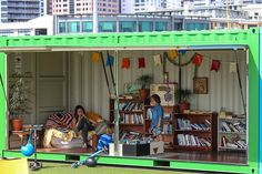 Auckland waterfront - Pop-up library in a shipping container. Uses a take a book / leave a book swap system of library discards. Artificial turf marks a little gathering spot in front of a shipping container library. Lilliputian furniture can be moved around to suit the sun.