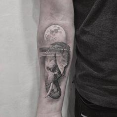 Double exposure elephant head tattoo on the right inner forearm.