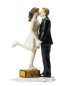 """A Kiss and We're Off!"" Caucasian Couple Wedding Cake Topper made of hand painted porcelain.  The bride is wearing a short white dress, white shoes, and she is standing on top of a suitcase. The groom is wearing a handsome black suit, holding his bride's hands, stealing a kiss from her before they run off on their honeymoon."