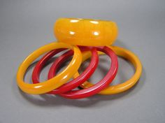 This delicious stack measures just a bit over 2 1/4 inches wide, and the end bangles have a curved angle that really makes this pop. They have all been tested and are guaranteed to be genuine bakelite/catalin. The large center one is so luminous, with transparent marbled orange, the reds are opaque and deep red, and the end pair are opaque as well. They are in very good shape with typical vintage wear, and the reds could use a quick polish with Brasso or any other metal polish. The ...