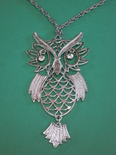 """Vintage Silver Tone Figural Owl Pendant Necklace. Large very ornate owl pendant is silver with dangling cubic zirconia eyes. Detailed feathers and body outline. Silver chain. Owl measures about 5"""" in length top to bottom, head measures approximately 2.75"""" wide and body is about 2.25"""" in width. Chain is silver with clasp closure and measures 12.25"""" long. Heavier weight pendant."""