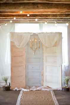 30 Wedding Light Ideas That Glow Magnificent ❤ wedding light white vintage door as a backdrop with an elegant chandelier and white cloth light bulbs and framed with white flowers in cans krystal healy photography ❤ See more: http://www.weddingforward.com/wedding-light-ideas/ #wedding #bride #weddingdecorations