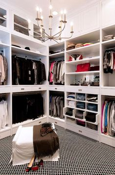 Chic walk in closet boasts floor to ceiling built ins fitted with glass cabinets, open shelving for sweaters, stacked clothes rails and pull out jean racks alongside a black and white carpeted floor.