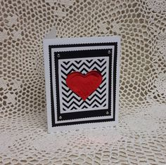 This striking Valentines Day card features a chevron panel die cut in white that is then triple matted with alternating black and white mats. Four pewter colored brads were added for embellishment. Center stage is a big heart die cut from shiny red foil paper. The inside of the card was left blank so you can add your own personal message.  The card measures approximately 4 X 5 1/2. A white envelope is included.
