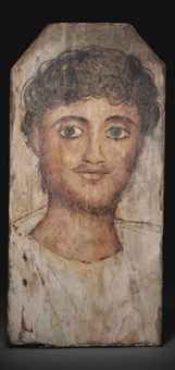 AN EGYPTIAN PAINTED WOOD MUMMY PORTRAIT OF A YOUNG MAN