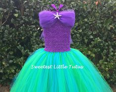 Welcome To Sweetest Little Tutus! **Please read my shop announcements before placing any orders to see current turnaround time.** This Ariel inspired tutu dress is perfect for any little girl that loves The Little Mermaid! All my tutu dresses include a lined crochet top for better coverage, extra warmth, and for overall added comfort. This Ariel dress includes 3 layers of emerald green and turquoise tulle for a full and fluffy tutu appearance. A satin purple ribbon on the lined purple…
