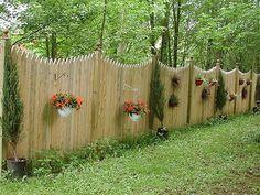 сплошной забор украшен горшками с цветами