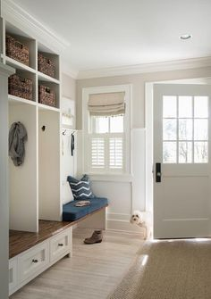 Beautifully designed white and tan mudroom is fitted with a wood mudroom bench fixed above white shelves and below open lockers fitted with stacked overhead shelving.