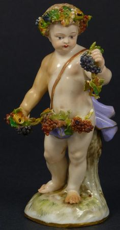 ANtique Meissen German porcelain cherub figure. Depicts a cherub with floral garland crown and grape clusters in hand. Part of the four season collection and represents the season of Autumn. 19th century 5 3/8 inches in height