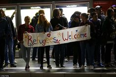 Greeting: Refugees were met by German well-wishers as they arrived in Frankfurt by train f...