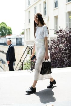 Womenswear Street Style by Ángel Robles. Fashion Photography from Paris Fashion Week. Minimal summer outfit with white midi skirt, t-shirt, black brogues and black leather bag, Paris.