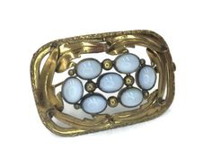 Wonderful brooch from around the Edwardian Era (early 1900s) set with gorgeous blue moonglow glass cabochons on stamped brass in leaves in a rectangular shape. Has a trombone clasp.  Measurements: 2 x a little over 1 1/4 Please be sure to check out my shop for a *~HUGE~* variety of vintage and antique jewelry that has FREE additional shipping.