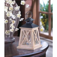 """This wooden candle lantern is the definition of classic country charm. White """"X"""" trim highlights the clear glass panels of this four-sided lantern, and the black roof features a hanging loop. Place the candle of your choice inside and enjoy the glow!  Wood, glass and iron."""