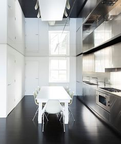 Mirrored ceiling in minimal kitchen space: not sure if I would do it but the creation of light and expanse of space is amazing.