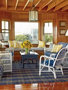 Pops of yellow color give this classic coastal living room a fresh look. Blue fabric, white-painted rattan, and yellow accents offer a bright contrast to the coziness of the wood in this Fire Island home. (Photo: Tria Giovan)