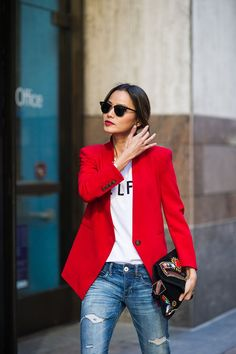 Rock a red blazer with blue distressed slim jeans to create a chic, glamorous look.   Shop this look on Lookastic: https://lookastic.com/women/looks/blazer-crew-neck-t-shirt-skinny-jeans/8131   — Red Blazer  — White and Black Print Crew-neck T-shirt  — Black Sunglasses  — Black Embroidered Suede Clutch  — Blue Ripped Skinny Jeans