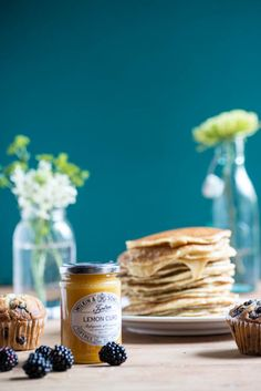Food & Prop Styling by Raleigh North Carolina designer & owner of the shop Gather Goods Co, Michelle Smith. Photography by Lissa Gotwals. A beautiful breakfast spread featuring a stack of pancakes, berries, and muffins and pretty flowers in glass vases.