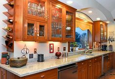Kitchen cabinets: Glass-faced kitchen cabinets with marble counter tops. Includes a wine rack on the outside of the cabinetry.