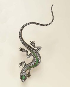 AN ANTIQUE DIAMOND AND EMERALD BROOCH   Designed as an old European-cut diamond and calibré-cut emerald lizard, with cabochon ruby eyes, the head enhanced by an oval-cut emerald, to the tail of flexible design, mounted in silver and gold, circa 1895