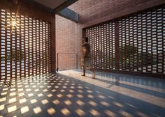 Brick grates set into the walls of a Bangkok house hide a series of outdoor spaces.