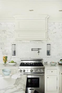 Gorgeous kitchen features creamy white cabinets paired with statuary marble countertops and ceiling height stuatuary marble subway tile backsplash.