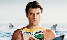 """""""I still buy actual books,"""" he says, holding up a worn paperback of Jaws and bringing it to his face with a deep inhale. """"The smell, having it in your hands—there's really no substitute."""" - Nathan Fillion Reveals Why He's Hooked on Books"""