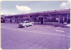 1984. Shops on corner of Chorley Ave and Waimumu Rd, Massey, Auckland, NZ. Right to left: Four Square grocer. Massey Meats butchery. Isalei hairdresser. A stationers and agency Post office opened on 16 August 1965 and closed 5th Feb 1988. Carey Agencies sewed caps in the far left shop in the 1980s. Barbara Webster ran Plunket in an office at the rear from 1972. It took 6 months for her to get a phone installed as there weren't enough lines in the area.