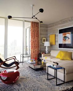 The lounge, designed by Tamzin Greenhill, features a sectional sofa and light fixture, both from J. Batchelor, and a stool from Ralph Pucci; the rug is by Luke Irwin