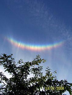 """Arco Circuncenital: apareciendo en el cielo como un """"arco iris al revés"""", el arco circuncenital se forma por la refracción de la luz a través de los microscópicos cristales de hielo horizontales que se forman en nubes específicas. El fenómeno está centrado en el cenit, paralelo al horizonte. Sus colores van del azul al rojo hacia el horizonte, y siempre en forma de un arco circular incompleto. Un círculo completo en una situación similar es el excepcionalmente raro arco Kern,..."""