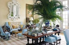 """""""If you have formal furniture and decide you would like a more tropical look for it, try covering the pieces in inexpensive cotton canvas or duck,"""" writes Bunny, pointing out the sky-blue slipcovers she used to ease up the sofas and chairs in the high-ceilinged island living room."""
