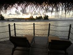 View at sunset from an Over-water Bungalow in Tikehau (Polynesian Islands).  Read a great review of the island and resort.
