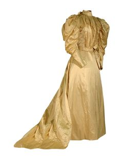 Beige Satin, 1895    Ola Brinkman wore this cream-colored satin gown at her wedding to G. Lorenzo Chapman on October 9, 1895, in Great Bend, Kansas.    This typical 1890s gown has the decade's exaggerated sleeves, known as leg-of-mutton for their resemblance to that cut of meat. The sleeves contain paper supports to maintain their fullness. The bodice's high collar is also typical of the decade, and is trimmed at back with a satin bow.