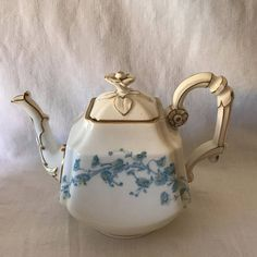 A Stunning set of Old Paris. This beautiful hand painted tea set is Exceptional. It is painted with blue flowers with yellow centers. They have a beautiful flower handle on the lids. It is a really beautiful set. It is trimmed around the edges in gold and there is minor gold loss. No chips, cracks or damage. This set dates to about 1870s. There are 12 snack plates and 6 each of the tea cups and saucers. The teapot is 7 1/2 tall and 9 from the handle to the spout. The creamer is 5 1/...