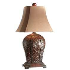 This masuline iron lamp features a mahogany finish with rust distressing and a beige wash. The brushed palomino sueded textile shade is a rectangular bell with clipped corners.