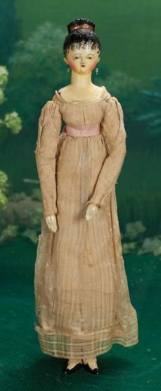 Early Grodnertal Wooden Lady circa 1820 with original early costume,and earrings. Shapely torso with modeled detail of bodice neckline, painted black hair with extravagantly-painted curls onto her forehead,with carved and painted gold-framed decorative comb at her crown, painted flat black shoes