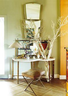 La casa de Laura Ponte Un rincón con un tocador y taburete de Duarte Pinto Coelho comprado en el rastrillo Nuevo Futuro y decorado con ramas con espejos de Tiempos Modernos.