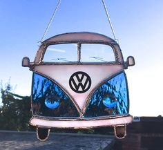 Volkswagen Camper van - everyones favourite camper! What a terrific and unique gift for the enthusiast of the Dub! It has been made using a lovely petrol blue rough rolled glass and also a very pale pink / white marl opaque glass. The details are very delicate windscreen wipers, a VW badge which is a wooden laser cut motif and the headlamps are two large glass beads. Made in the traditional Tiffany style with stained glass, copper foiling and a bright silver solder. Attached is a silver…