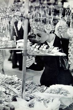 A woman shops for silverware, Florence, Italy, 1950s. Photo by Henri Cartier-Bresson.