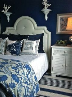 Coastal Bedroom with a Nautical Feel with Dark Blue Wall Color but Feminine Headboard and Ornate Sconces with Corals give this Coastal Bedroom a Beach Vibe.