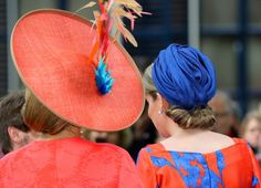 Queens Máxmia and Mathilde in colour-coordinated outfits in The Hague 20/05/15, The two Queens both opted for bright coloured outfits by their common favourite brand Natan. Queen Mathilde donned an orange and blue dress that she paired with a blue Fabienne Delvigne hat, a blue clutch and a pair of matching heels. Queen Máxima wore an orange dress with beige accessories except for her large hat, which was orange with a trendy feature of orange and blue feathers matching the Belgian Queen's…