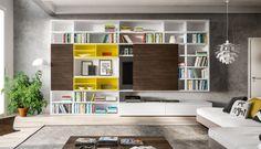 Parete attrezzata a spalla con libreria dotata di ante e due basi con cassetti a terra.