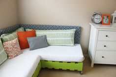 Brightly-colored toddler beds (could be used as a couch, too). There's also a tutorial for how to make a headboard.