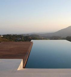 The dramatic horizon line of this infinity pool creates a stunning view of the valley and mountains beyond. The pool is framed by a multi-level deck of stone and wood, conforming to its natural surroundings and retaining a simple, yet oh-so-tantalizing design.